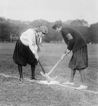 Face-off - Two female field hockey players prepare to start or resume the match with a bully-off in the centre of the pitch.