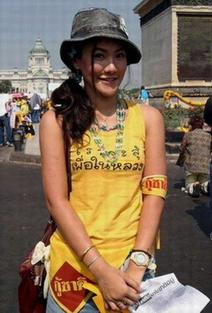 "2005–06 Thai political crisis - An anti-Thaksin protester wearing the anti-Thaksin slogan ""Fight for the King."" Her shirt is royal yellow, the official colour of the PAD."