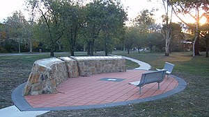 An ellipse of orange pavers surrounded by a grey border, with a man-made rock structure on one side of the ellipse displaying plaques. On the other side are two bench seats. Grass surrounds the ellipse and trees can be seen in the background.