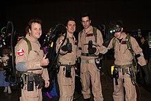 Photograph of four men dressed as Ghostbusters in khaki uniforms