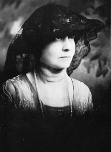 Black-and-white headshot of a woman wearing a hat draped with lace