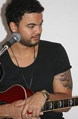 A man wearing a black shirt, holding a guitar