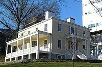 Žlutý dům se schodištěm k předním dveřím a verandou na boku