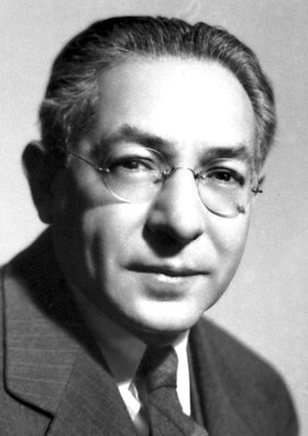 Head and shoulders of man in suit and tie wearing glasses