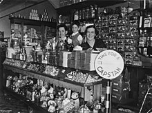 Stacks of chocolate bars line the top of the counter above an assortment of lollies in the glass cabinet. Ornaments and toys are on the lower shelf of the counter. Rows of tinned food, jars and cardboard boxes line the shelves behind the family. A large sign to the right of the counter advertises Capstan cigarettes.