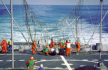 The rear deck of ship, with a large partially erect net visible near the center of the image. Many men in orange suits are working to free a white drone entangled in the net.