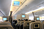Airliner cabin. Rows of seats arranged between two aisles. Each seatback has a monitor; additional monitors hang from ceiling.