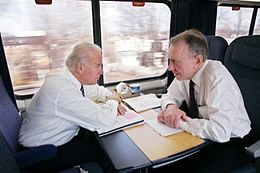 Two men speaking to each other in a compartment on a train. Sitting in blue seats with paperwork spread out on tables in front of them, the man on the left has white hair and the man on the right has gray hair. Both wear white dress shirts, black pants and ties.