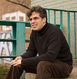 The author Jonathan Lethem, sitting on the bank of the canal