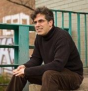 Jonathan Lethem sitting on steps in Brooklyn in a turtleneck