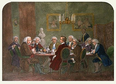 Dining room with nine men seated around a table. The dinner has been finished, and a large man at the head talks and gesticulates while the others eagerly listen. The men wear wigs and clothing of late 18th century Britain, and the furniture, hangings, and chandelier are of similar vintage. A liveried servant is entering with a tray bearing two high-shouldered decanters of wine.