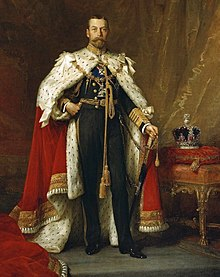 Full-length portrait in oils of King George V of the United Kingdom. He wears naval uniform under an ermine cape, and beside him a jewelled crown stands on a table.