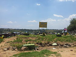 "A community painted sign, reading ""Kya Sands Formal Settlement, Please RDP"""