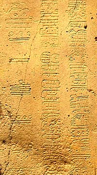 Detail showing three columns of glyphs from La Mojarra Stela 1.  The left column uses Maya numerals to show a Long Count date of 8.5.16.9.7, or 156 CE.