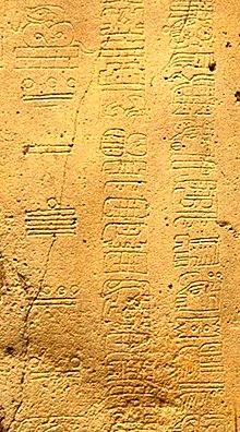 Dettaglio di incisione che mostra tre colonne di glifi dalla Stele di La Mojarra 1. Nella colonna di sinistra sono utilizzati numerali Maya per mostrare la data a Conto Lungo di 8.5.16.9.7, o 156 CE.
