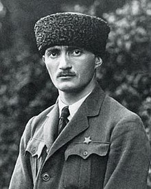 Image of a man from the shoulders up. He is wearing a fur hat and looks directly at the camera
