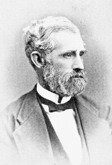 Head and shoulders photograph of a man in a Victorian suit. He has a white beard and large mustache He wears a serious expression and is looking to the left.