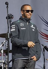 Lewis Hamilton wearing sunglasses looking off to his left