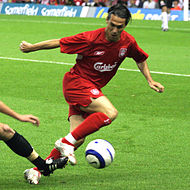 A coloured photograph of a man controlling a football. He is dressed in a red kit.