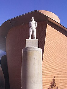 A stone statue of Shakur standing on a tall stone pillar in front of the MARTa Herford museum