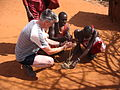 Maasai people and a tourist lighting a fire in a Maasai village on the A109 road, Kenya.jpg
