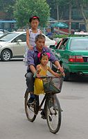 Man Riding a bike with two kids.jpg