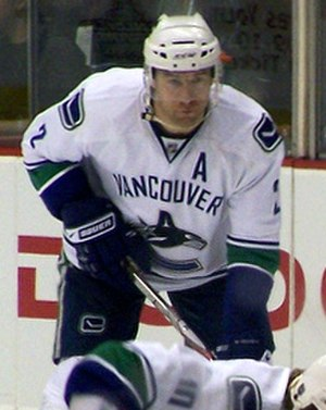 "Mattias Öhlund -  alt = An ice hockey player leans forward with his stick. He has a serious look of concentration on his face as he looks into the distance. He wears skates, gauntlets, a helmet with a visor and a sweater with a stylized ""C"" shaped like a whale. Above the logo is the word ""Vancouver,"" and a large ""A"" directly under his left shoulder."
