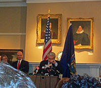 A man at a lectern with his hand to his face. Behind him are the United States and New York flags and a wall with portrait paintings