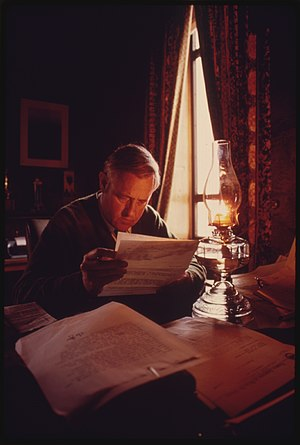 Tom McCall - Governor McCall reads by kerosene lamp to draw attention to the Energy Crisis, 1973