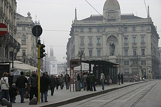 Cordusio (Milan Metro) - Entrance to the metro station beside the northbound tram stop on Via Dante. The Assicurazioni Generali building is in the background.