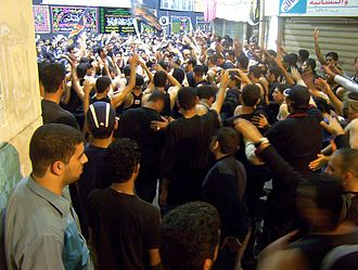 Shia Muslims in Bahrain strike their chests during Muharram in remembrance of Imam Hussain Muharram procession 2, Manama, Bahrain (Feb 2005).jpg