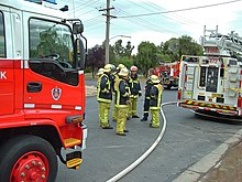 New South Wales Fire Brigade Station Officer Red Helmet And Firefighters Yellow Helmets