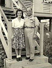 Informal full-length portrait of woman in skirt and blouse and man in light-coloured military uniform standing on steps in front of a building