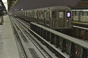 33rd Street–Rawson Street (IRT Flushing Line) - An R62A express train bypasses the station during a light blizzard in February 2013.
