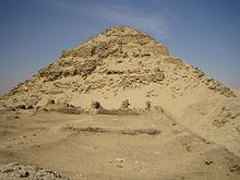Ruins of a pyramid, its shape well preserved, in the desert.