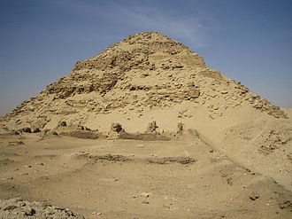 Large but ruined pyramid made of limestone and bricks in the desert.