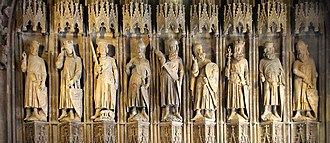 "Nine Worthies - The thirteenth century carving ""Nine Good Heroes"" (known as ""Neun Gute Helden"" in the original German) at City Hall in Cologne, Germany, is the earliest known representation of the Nine Worthies. From left to right are the three Christians: Charlemagne bearing an eagle upon his shield, King Arthur displaying three crowns, and Godfrey of Bouillon with a dog lying before him; then the three pagans: Julius Caesar, Hector, and Alexander the Great bearing a griffon upon his shield; and lastly the three Jews: David holding a sceptre, Joshua, and Judas Maccabeus."