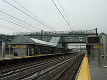 "A train station with overhead lines and four tracks between two sheltered platforms, both wet, under cloudy skies. Letters across an overhead walkway spell out ""Newark Liberty International Airport"""