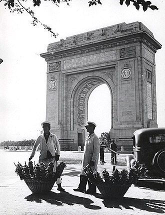 Memorial gates and arches - Pretzel vendors in front of the Romanian Triumphal Arch in Bucharest.