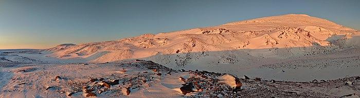 Montagne arrondie à peine éclairée de rose par le Soleil et couverte de neige.