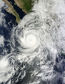 A well developed hurricane approaching Baja California, Mexico, from the south. It features a mostly circular cloud mass surrounding a defined eye.
