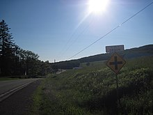 "A winding country road with green trees growing on the right and a farm on the left. A white sign with blue lettering atop an intersection marker reads, ""VILLAGE OF ORSON."""