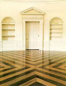 Oval Office floor, replaced during the administration of George W. Bush. Based on a 1933 design by Eric Gugler, the 2005 installation is arranged in a contrasting cross pattern of quarter-sawn oak and walnut. Most of the floor is usually covered with an elliptical rug.