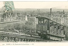A sepia postcard taken at an angle to the track showing one of the first funicular's cabins. Its stepped compartments are clearly shown. In the background is a panorama of Paris