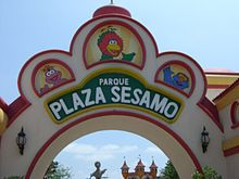 "A view of upper part of a sign, mostly white, with pictures of three characters above the words ""Parque Plaza Sesamo"" in large, white letters."