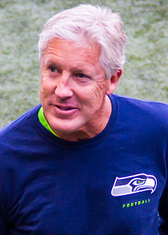 Color head-and-shoulders photograph of silver-haired Pete Carroll in dark blue sport shirt with Seattle Seahawks logo on left breast.