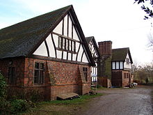 A house with three gabled bays seen from an angle. The outer bays have lower storeys in brick with a timber-framed gable. The middle gable is almost completely timber-framed on a low brick plinth. Between the second and third bays is a tall chimney stack.