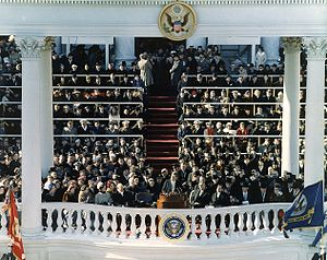 Inauguration of John F. Kennedy - View of the extended East Front of the Capitol where the inauguration was held. President Kennedy is in the center delivering his inaugural address, with Vice-President Johnson and official and invited guests sitting behind him.