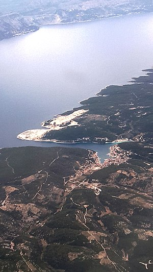 Pučišća - Aearial view of Pučišća. The top of the picture points north east. To the upper left is the Dalmatian mainland, separated through the Brač channel. The white area above the mouth of the bay of Pučišća is the quarry Veselje. The bay splits to Stipinska luka on the right and Pučiški dolac to the bottom.