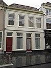 foto van Huis met witgeverfde lijstgevel en zadeldak met rode pannen
